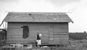 1925-09-21 Leone and Merna Hansen in front of the little house, on the west side, as it was being built, holding Merna with Pat alongside