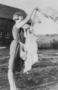 1928 Leone Hansen hanging clothes with Morton's barn in behind her