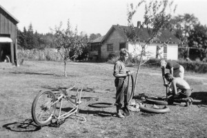 1944-08 Robert, Norman, Roald Hansen repairing tire on Silver King bicycle