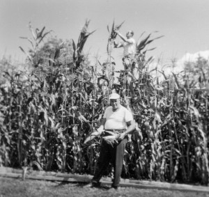 1965-08-29 Rollin standing in front of corn showing very tall Peruvian corn, while Don is standing on a six-foot ladder